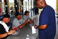 Brees signs autographs at Guantanamo Bay Naval Base on June 29, 2009, along with fellow NFL players Billy Miller and Donnie Edwards.