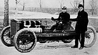 Henry Ford standing next to Oldfield's first car in 1902