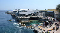 The Monterey Bay Aquarium, viewed from the back. The shallow area behind the rocks was turned into a whale tank via special effects; other changes included the addition of the San Francisco skyline in the background.