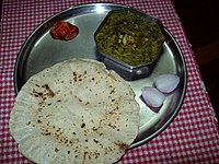A typical simple Maharashtrian meal with bhaaji, bhakari, raw onion and pickle