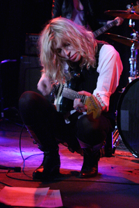 Love, pictured playing a Fender Mustang in 2012, has often played both Fender and Rickenbacker guitars throughout her career