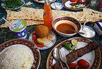 A table of some of Tabriz traditional foods (köfte and syrup with sangak and Bonab Kababi with rice)