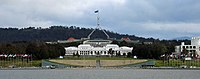 Two of Canberra's best-known landmarks, Parliament House and Old Parliament House (foreground). Commonwealth Place runs alongside the lake and includes the International Flag Display. Questacon is on the right.