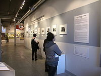 """Visitors viewing """"Life and Death in Black and White: AIDS Direct Action in San Francisco, 1985–1990"""" in the Front Gallery of The GLBT History Museum (March 2012)."""