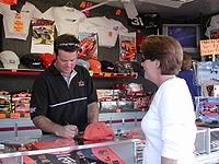 Gordon signing autographs at his souvenir trailer, a very common sight during most NASCAR weekends