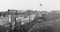 """The original ad-covered Green Monster in 1914, with """"overflow"""" fan seating in front of the wall's base, atop """"Duffy's Cliff"""" (seen in the distance, nearest the flagpole)."""