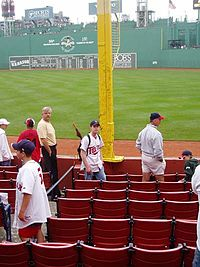 The bottom portion of Pesky's Pole, with the Green Monster in the background and Fenway Park's right field seats in the foreground.