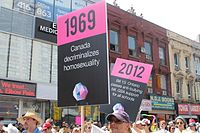 Marchers at Pride Toronto 2014 with signs commemorating significant events in LGBT history in Canada. In 2014, Toronto hosted WorldPride.