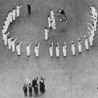 """Bellamy salutes in 1917 at a Fifth Avenue, New York ceremony opposite the Union League Club reviewing stand during the recent """"Wake Up, America"""" celebration where thousands marched in the procession"""
