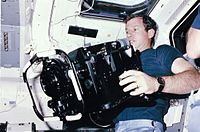 STS 41-C mission specialist Terry J. Hart, holds a 70-pound IMAX camera in the mid deck of the space shuttle Challenger in 1984.