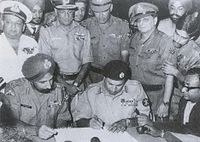 Pakistan's Lt. Gen. A. A. K. Niazi signing the instrument of surrender in Dhaka on 16 December 1971, in the presence of India's Lt. Gen. Aurora. Standing behind them are officers of India's Army, Navy and Air Force. The 1971 War directly involved participation of all three arms of Indian Armed Forces.