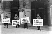 """Nazi boycott of Jewish businesses: SA troopers urge a boycott outside Israel's Department Store, Berlin, 1 April 1933. All signs read: """"Germans! Defend yourselves! Don't buy from Jews."""""""