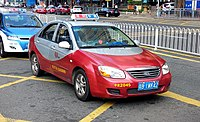 A red petrol fuel taxi with an electric blue and white taxi behind it