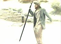 Still film image showing Torgo wearing a jacket, shirt, and pants bulging at the thighs, carrying a walking staff.
