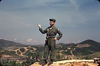 Dukakis off duty at a gun emplacement overlooking UN Command Military Armistice Commission base camp at Munsan-ni Korea 1956.