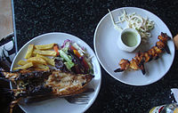 {{small Left}} Tandoori lobster with fries and vegetables.