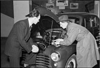 A buyer and seller looking under the bonnet of a Vauxhall at a dealership in Denmark in the 1950s