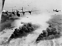 15th Air Force B-24s fly through flak and over the destruction created by preceding waves of bombers.