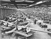 """AAF Antisubmarine Command (AAFAC) modifications at the Consolidated-Vultee Plant, Fort Worth, Texas in the foreground in the olive drab and white paint scheme. To the rear of this front line are partly assembled C-87 """"Liberator Express Transports""""."""