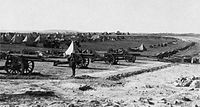 British artillery battery on Mount Scopus in the Battle of Jerusalem, 1917. Foreground, a battery of 16 heavy guns. Background, conical tents and support vehicles.
