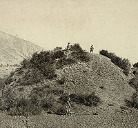 This general view of the unexcavated Buddhist stupa near Baramulla, with two figures standing on the summit, and another at the base with measuring scales, was taken by John Burke in 1868. The stupa, which was later excavated, dates to 500 CE.