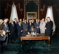 President Kennedy signs the Partial Test Ban Treaty, a major milestone in early nuclear disarmament in the Nuclear Age