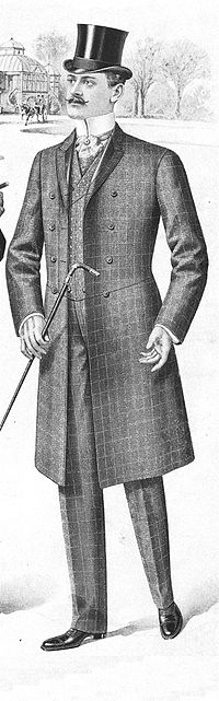 An informal checked frock coat suit with odd waistcoat. The foreparts are connected by a chain link.