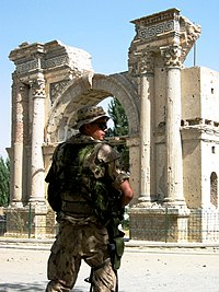 An ISAF soldier standing by the ruins of the Victory Arch in 2004, before its renovation