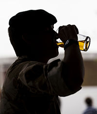 A British soldier drinks a glass of beer after his return from Afghanistan. Fighting in wars and drinking alcohol are both traditionally masculine activities in many cultures.