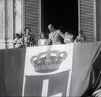 King Umberto II and the royal family of Italy behind of the Flag of Kingdom of Italy