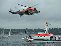 A cruiser of the DGzRS and a SeaKing helicopter of the German Navy