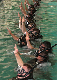 """Search and Rescue students give the """"I am all right"""" signal to let the SAR instructors know that they are ready for further instructions at the pool on board Naval Station San Diego."""