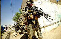 U.S. soldiers from the 6th Infantry Regiment taking up positions on a street corner during a foot patrol in Ramadi, Iraq