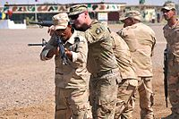 A trainer with Company A, 1st Battalion 502nd Infantry Regiment, Task Force Strike, 101st Airborne Division assisting Iraqi army ranger students during a room clearing drill at Camp Taji, Iraq on 18 July 2016