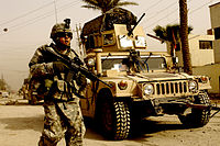 A U.S. soldier on patrol with the support of a Humvee vehicle