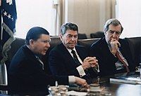 Reagan (center) receives the Tower Commission Report regarding the Iran-Contra affair in the Cabinet Room with John Tower (left) and Edmund Muskie (right)