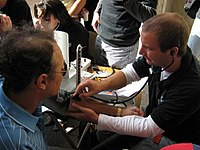 A medical student checking blood pressure on an awareness drive