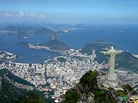 A panoramic view of the statue at the top of Corcovado Mountain with Sugarloaf Mountain (centre) and Guanabara Bay in the background.