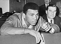 Ali watches replay of his 1966 title fight against Henry Cooper.