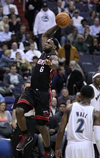 James goes in for a slam dunk as a member of the Miami Heat as John Wall of the Washington Wizards looks on in March 2011.