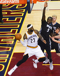 James throws a pass as Gorgui Dieng defends in December 2014. Later that season, James reached several passing milestones, including becoming the Cavaliers' all-time assists leader.