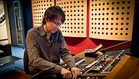 A studio engineer working with an audio mixer in a recording studio.