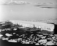 An iceberg being pushed out of a shipping lane by (L to R),, and near McMurdo Station, Antarctica, 1965