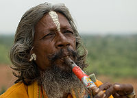 A man playing flute in Orchha, with a white tilak on his forehead, and holy saffron-coloured clothes.