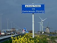The Netherlands is a heavily developed country. Shown here is a motorway passing by a polder with a drainage windmill, and two wind turbines in the background.