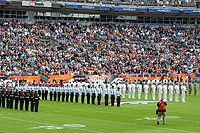 Service members of the U.S. at an American football event, L-R: U.S. Marine Corps, U.S. Air Force, U.S. Navy and U.S. Army personnel