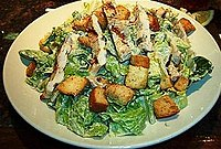 A Caesar salad containing croutons, Parmesan cheese, lemon juice, olive oil, Worcestershire, and pepper.