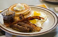 American style breakfast with pancakes, maple syrup, sausage links, bacon strips, and fried eggs.