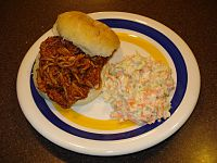 A barbecue pulled-pork sandwich with a side of coleslaw.