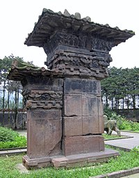 A stone-carved pillar-gate, or que (闕), 6 m in total height, located at the tomb of Gao Yi in Ya'an, Sichuan province, Eastern Han Dynasty (25–220 AD); notice the stone-carved decorations of roof tile eaves, despite the fact that Han Dynasty stone que (part of the walled structures around tomb entrances) lacked wooden or ceramic components (but often imitated wooden buildings with ceramic roof tiles).